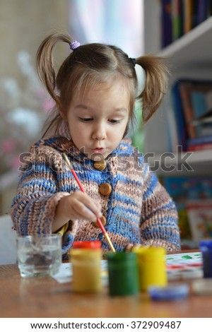 Little girl drawing with paints - stock photo