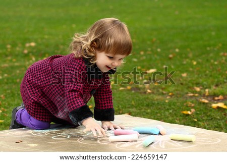 Little girl draws colored chalks standing on her knees on natural background outdoor - stock photo
