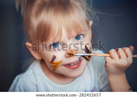 little girl draws on her face with a brush and paint - stock photo