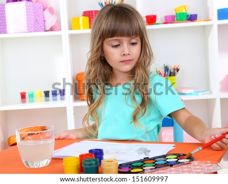 Little girl draws sitting at table in room on shelves background - stock photo