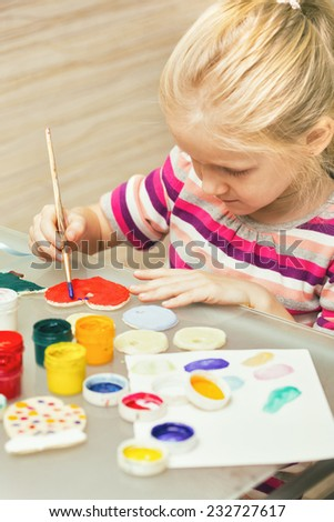 little girl draws sitting at the table  - stock photo