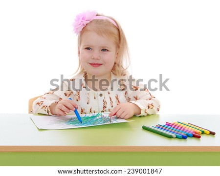 Little girl draws with markers while sitting at the table . Studio photo, isolated on white background. - stock photo