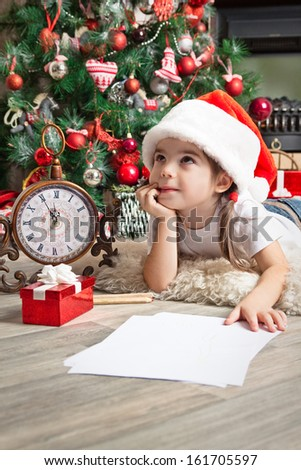 Little girl dreams about the gift and writes letter to Santa near christmas tree - stock photo