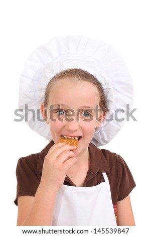 Little girl dressed as a chef eats a cookie - stock photo