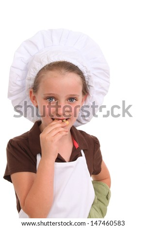 Little girl dressed as a cook eats a cookie - stock photo