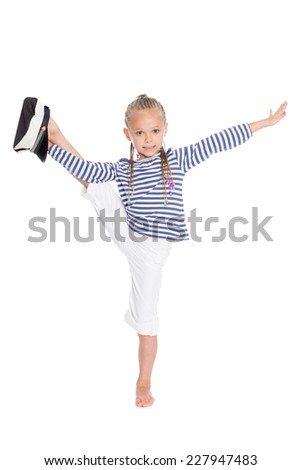 Little girl dressed as a sailor boy performs gymnastic exercise. Girl is six years old.  - stock photo