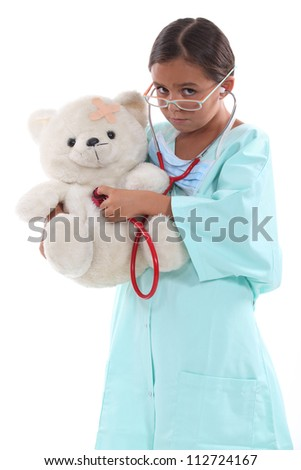 Little girl dressed as nurse holding teddy bear - stock photo