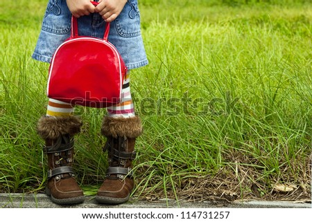 Little girl dressed in striped tights and a denim skirt is standing by a field and holding a red bag - stock photo