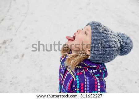 Little girl dressed in winter clothes catching snowflakes with her tongue while walking through falling snow. Winter fun. Close up.   - stock photo