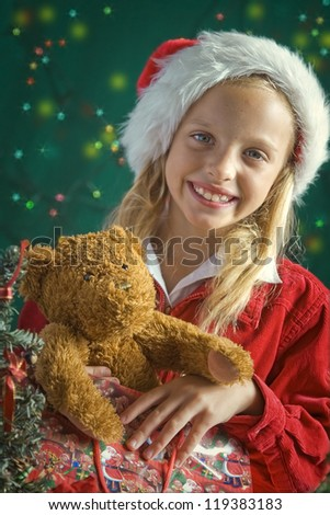 Little girl dressed up as Santa on green background - stock photo