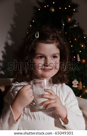 Little girl drinking a glass of milk at Christmas night - stock photo