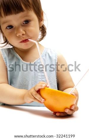 little girl drinking a grapefruit juice - stock photo