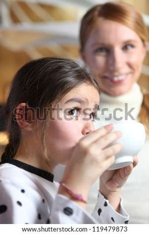 Little girl drinking from breakfast bowl - stock photo