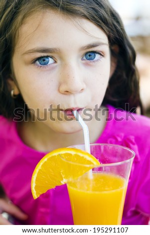 Little girl drinking orange juice from straw - stock photo