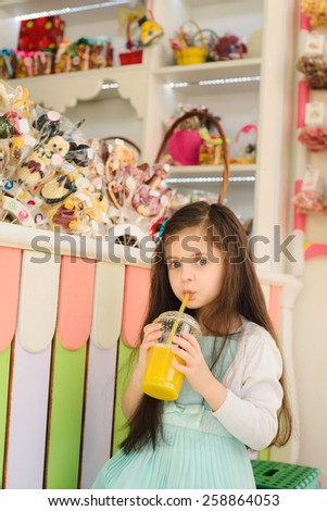 Little girl drinking orange juice through straw and looking at camera - stock photo