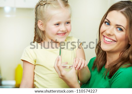 Little girl drinking water in kitchen with young mother. - stock photo