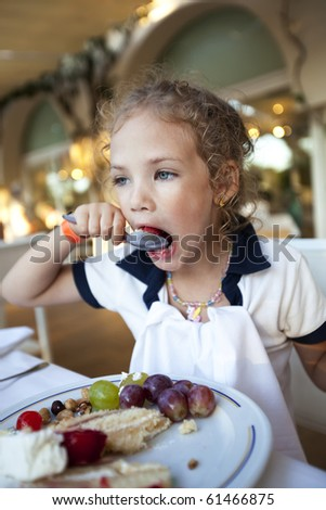little girl eating a cake at the restaurant - stock photo