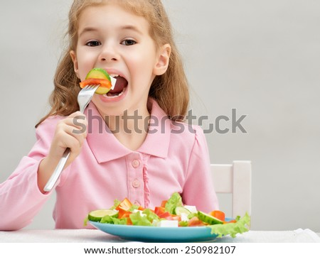 little girl eating a fresh salad - stock photo