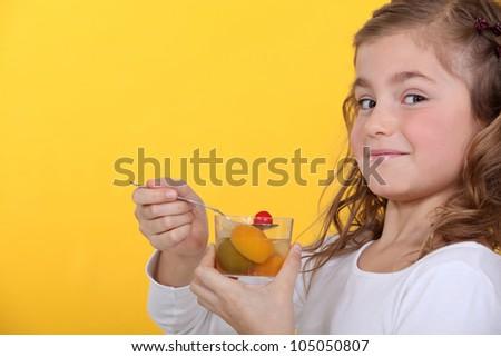 little girl eating a fruit salad - stock photo