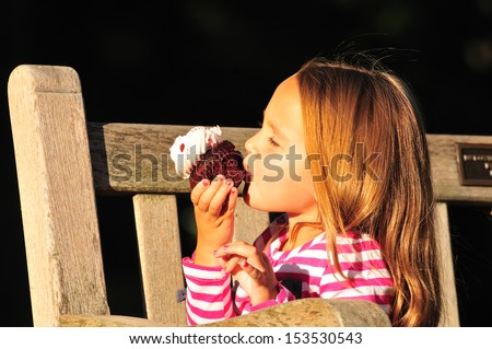 little girl eating a red velvet cupcake with cream cheese icing - stock photo