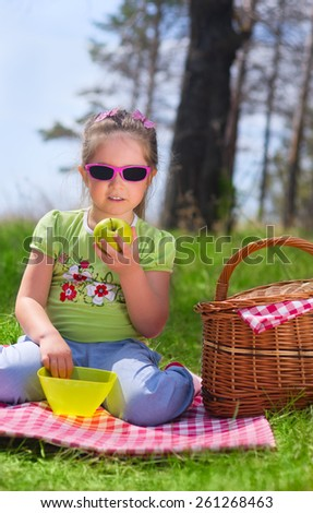 Little girl eating apple at picnic in the woods - stock photo