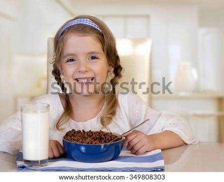 Little girl eating breakfast glass of milk & corn snack.Small kids' healthy nutrition. - stock photo