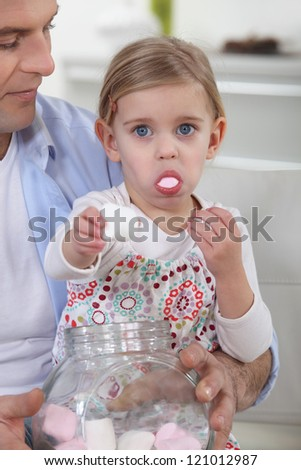 Little girl eating candy - stock photo