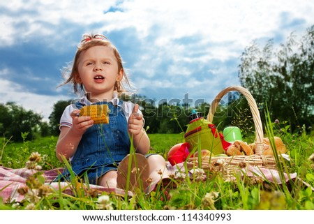 little girl eating corn on picnic in the park - stock photo