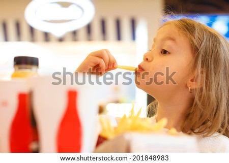 Little girl eating fast food  - stock photo