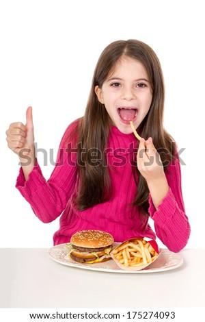 little girl eating hamburger  - stock photo