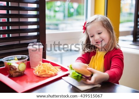 Little girl eating hamburger and French fries in a fast food restaurant. Child having sandwich and potato chips for lunch. Kids eat unhealthy fat food. Grilled fastfood sandwich for children. - stock photo