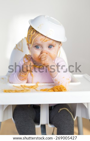 Little Girl Eating her dinner and making a mess - stock photo