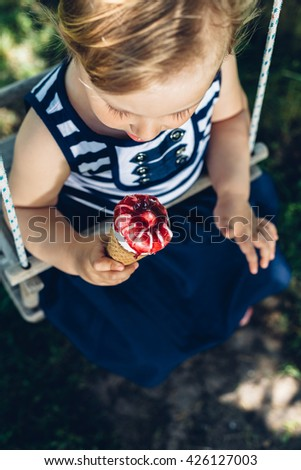 Little girl eating ice cream on a swing with copy space - stock photo