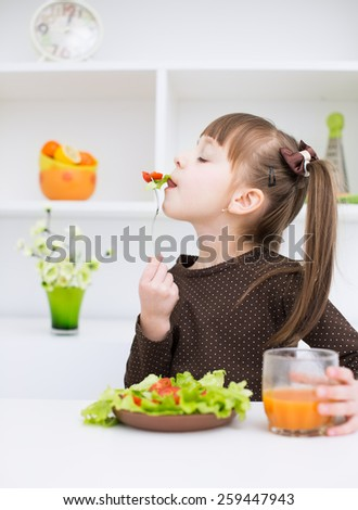 Little girl eating vegetable salad - stock photo