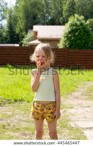 Little girl eats a red apple outdoor - stock photo