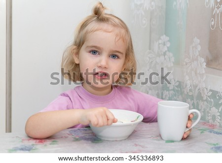 Little girl eats porridge from a plate sitting at the table. - stock photo