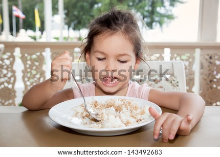 Little girl eats rice in a summer cafe - stock photo