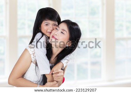 Little girl embrace her mother while smiling and looking at camera in home - stock photo