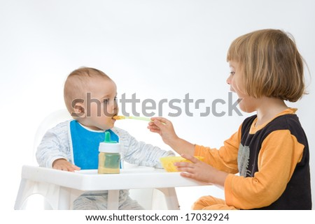 little girl encouraging her baby brother to eat - stock photo