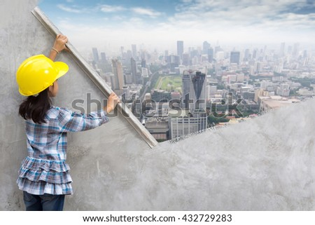 Little girl engineering ideas concept with hand holding plastering tools renovating a house. With painting modern city skyline, cityscape, building, skyscraper on wall - stock photo
