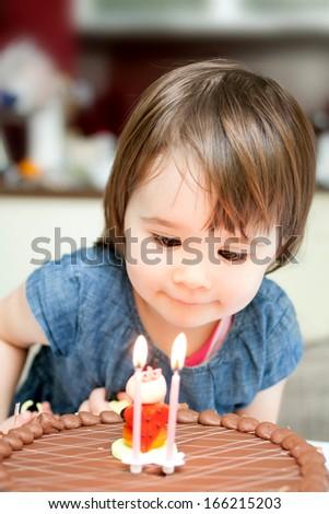 Little girl enjoying her birthday cake.  - stock photo