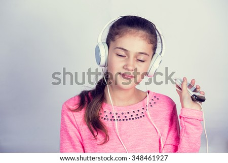 Little girl enjoying music in headphones at home relaxing. Relaxed little girl listening to music with earphones  looking serene and happy. - stock photo