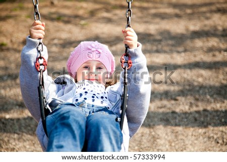 Little girl enjoying the swing in a spring day in the park. - stock photo