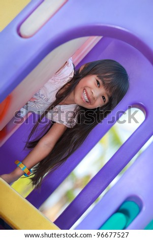 Little girl enjoys playing in a children playground - stock photo