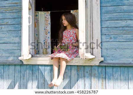 Little girl expecting someone sitting on the sill of the country house window - stock photo