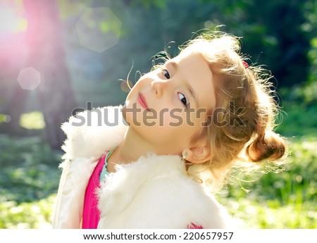 Little girl face closeup. Female child outdoors at sunlight.Spring season. - stock photo