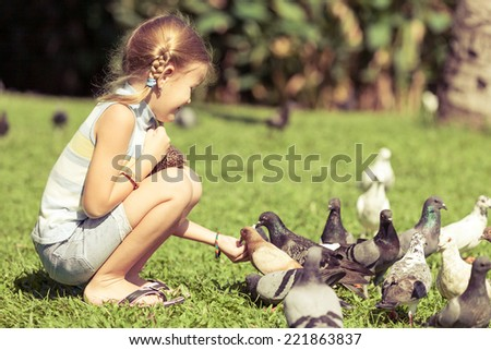 little girl feeding pigeons in the park at the day time - stock photo