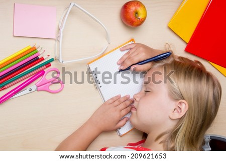 little girl fell asleep on the desk from fatigue lessons - stock photo