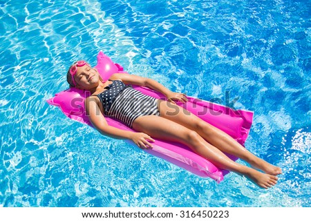 little girl floats on an inflatable mattress in the pool - stock photo