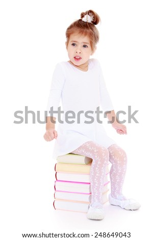 little girl froze while sitting on a stack of books.Isolated on white background, Lotus Children's Center - stock photo